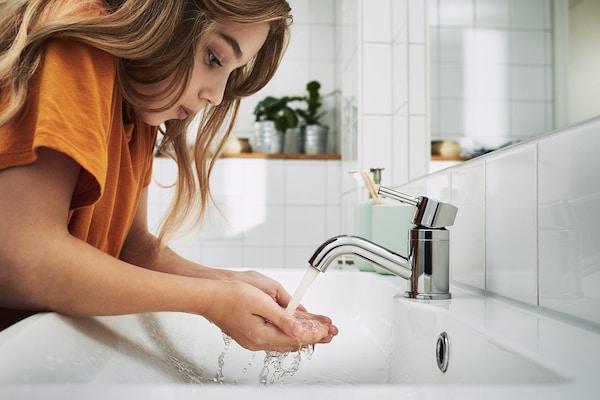 Mladá dívka v oranžovém tričku, si napouští do dlaní vodu, vycházející z koupelnové baterie.
