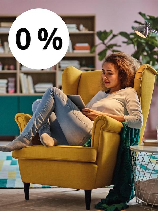 Mladá žena sedí na žlutém ušákovi STRANDMON a prohlíží si katalog.