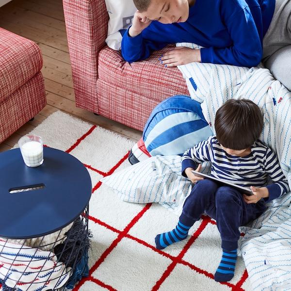 Młody chłopiec z tabletem w ręce, siedzący na narożniku kołdry spadającej ze sofy. Starszy członek rodziny obserwuje z sofy.