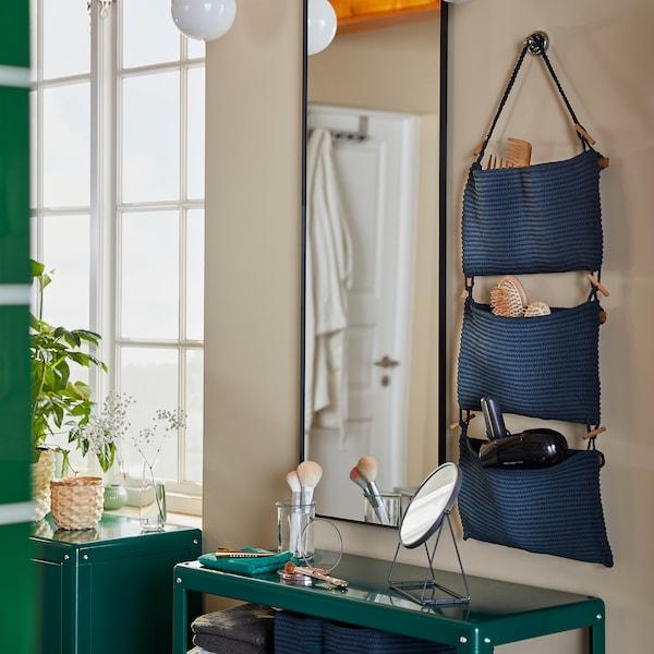 منصة تجميل في الحمام تتألف من وحدة تخزين NORDRANA معلقة ومرآة مثبتة على حائط ووحدة رفوف خضراء.