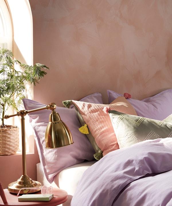MOAKAJSA/モーアカイサとKLARAFINA/クララフィーナ クッションカバーを使用したクッションが枕やベッドリネンに混ざって置かれている、日の当たるベッド。