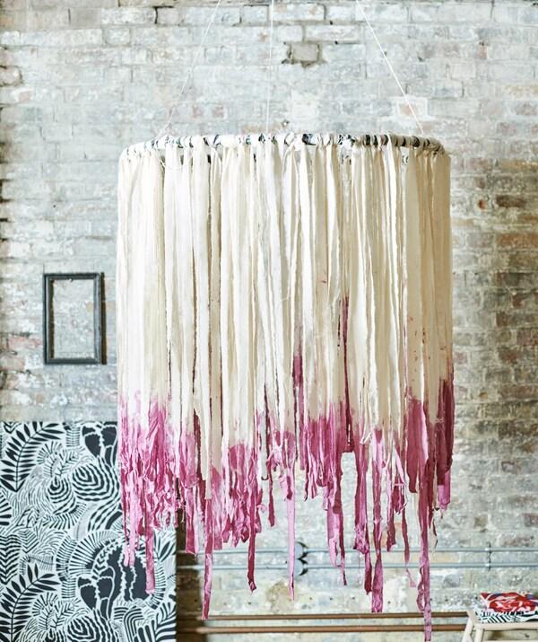 Мобиль в стиле бохо висит у кирпичной стены. Обруч украшен полосками белой ткани с розовыми кончиками, похожими на кисточки.