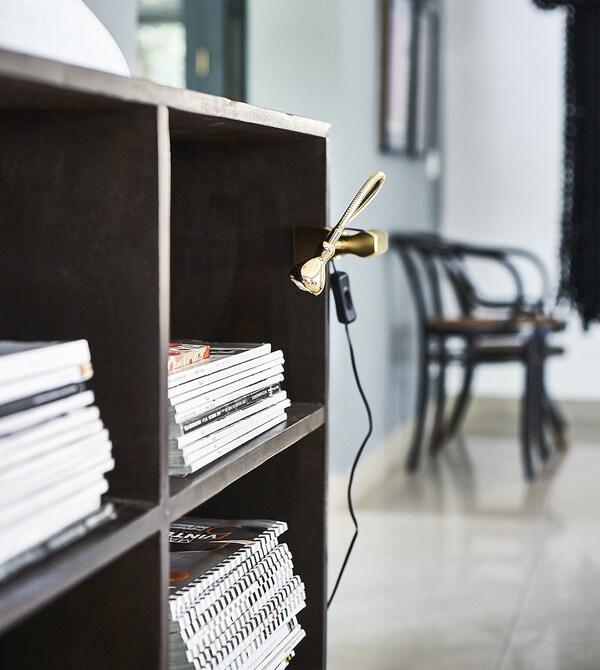 Mobile con riviste e una lampada a morsetto - IKEA