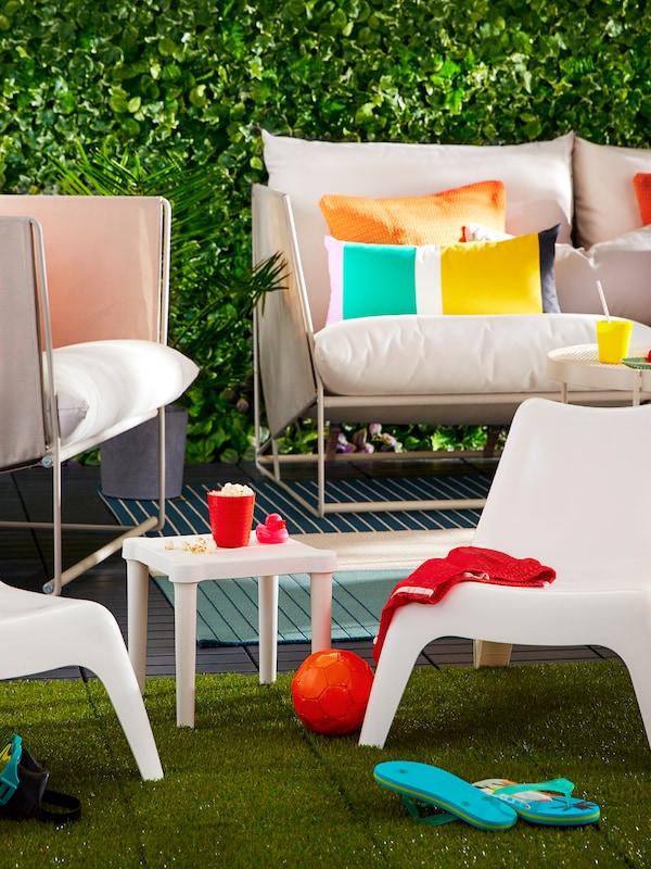 Mobilierul de exterior format din canapea și fotoliu, scaune pentru copii și masă cu perne și diferite obiecte.