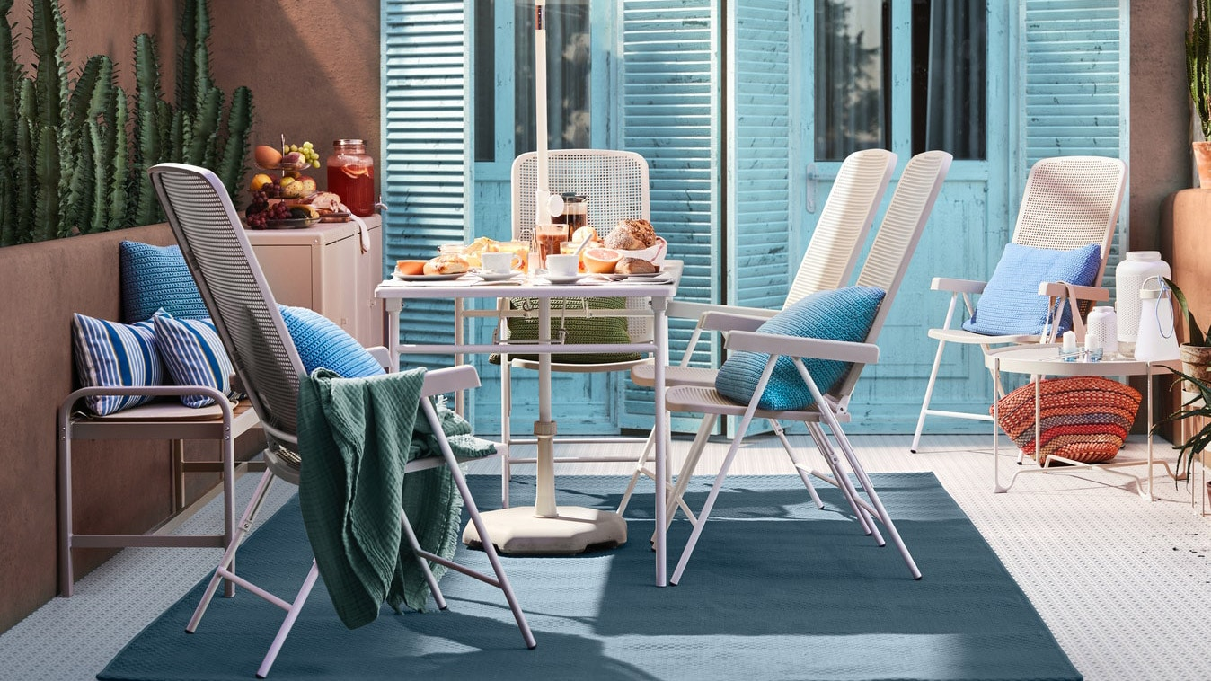 Møbler fra TORPARÖ serien der står udenfor på en terrasse foran lyseblå havedøre.