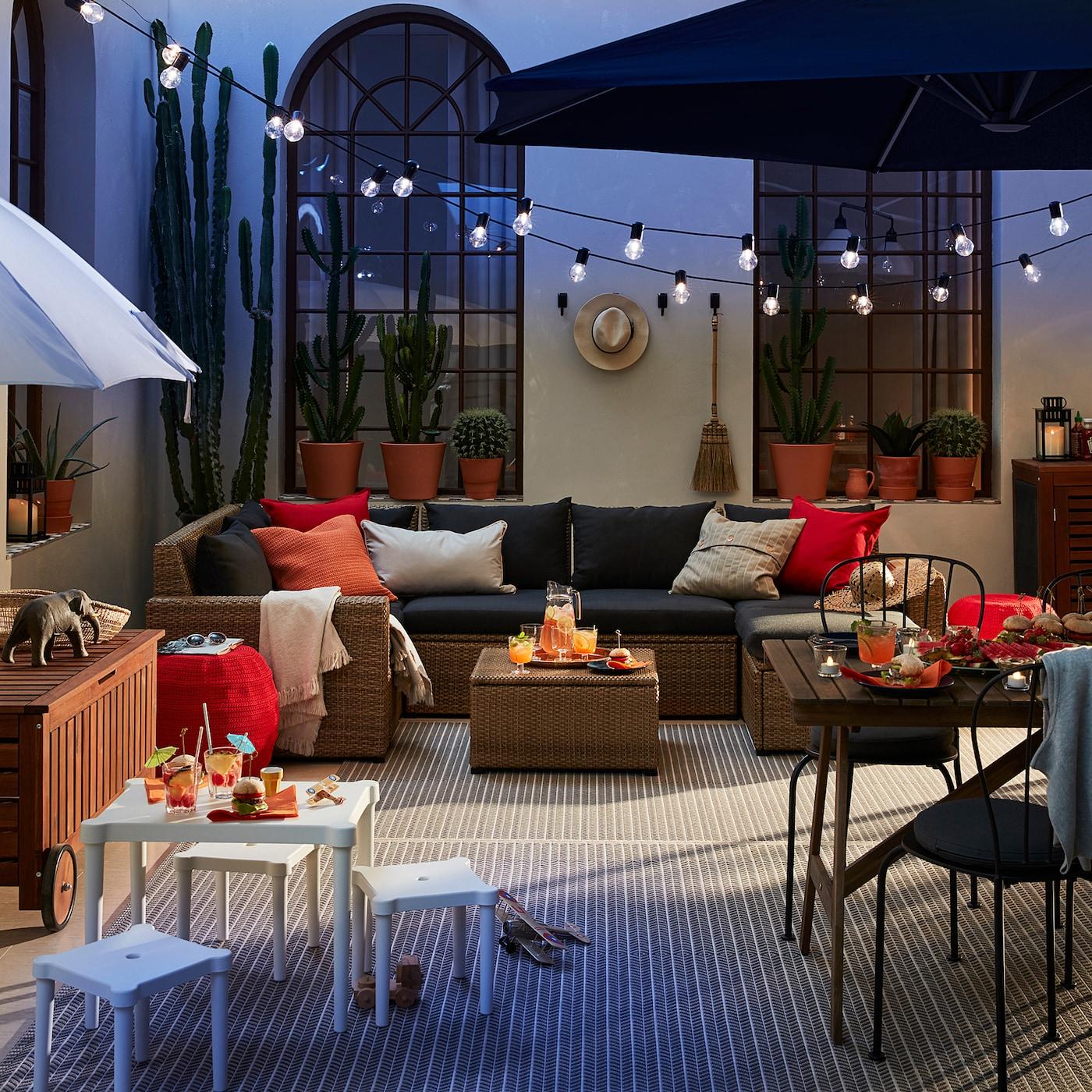 Modern, gemütlich gestaltete Terrasse mit Rattansitzmöbeln, Gartenservierwagen, Lichterketten & Kakteen.