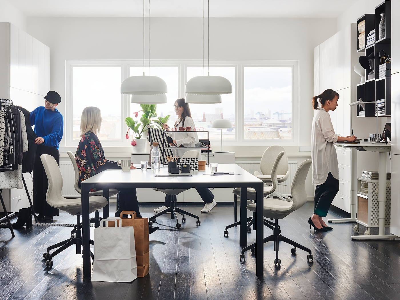 Moderná biela kancelária s bielymi stolmi BEKANT s nastaviteľnou výškou a čiernymi policovými dielmi.