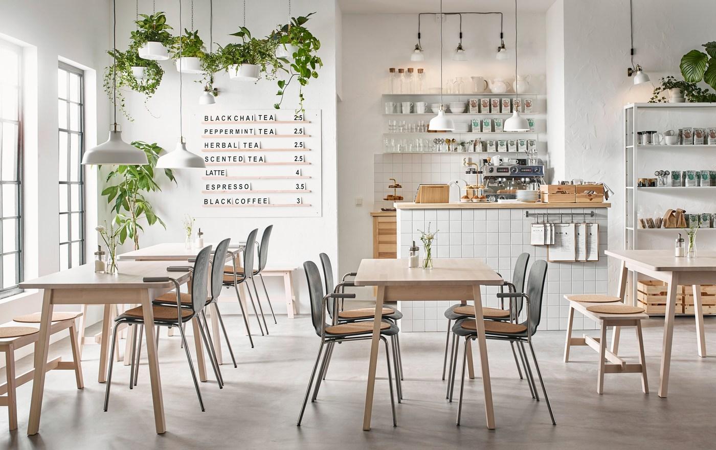 Moderná kaviareň v béžovej, čiernej a bielej farbe so stolmi NORRÅKER z bielej brezy a stoličkami SVENBERTIL v čiernej farbe a farbe chrómu.