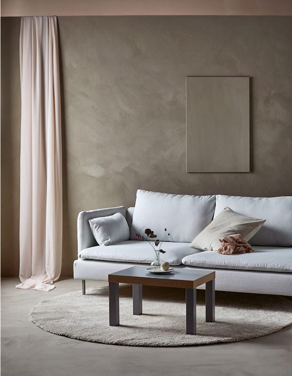 Moderne sofa i en minimalistisk stue med et enkelt kunstværk på væggen og et enkelt sofabord