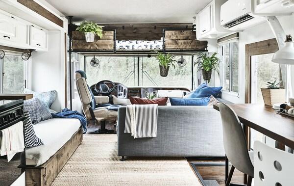 Moderner mit Holzmöbeln gestalteter Küchen- & Wohnbereich hinter dem Steuer eines Wohnmobils