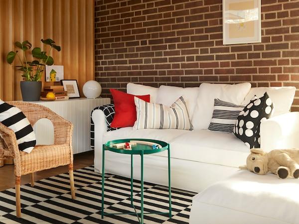 Modernt vardagsrum med en cremevit GRÖNLID bäddsoffa och schäslong på en randig STOCKHOLM matta.