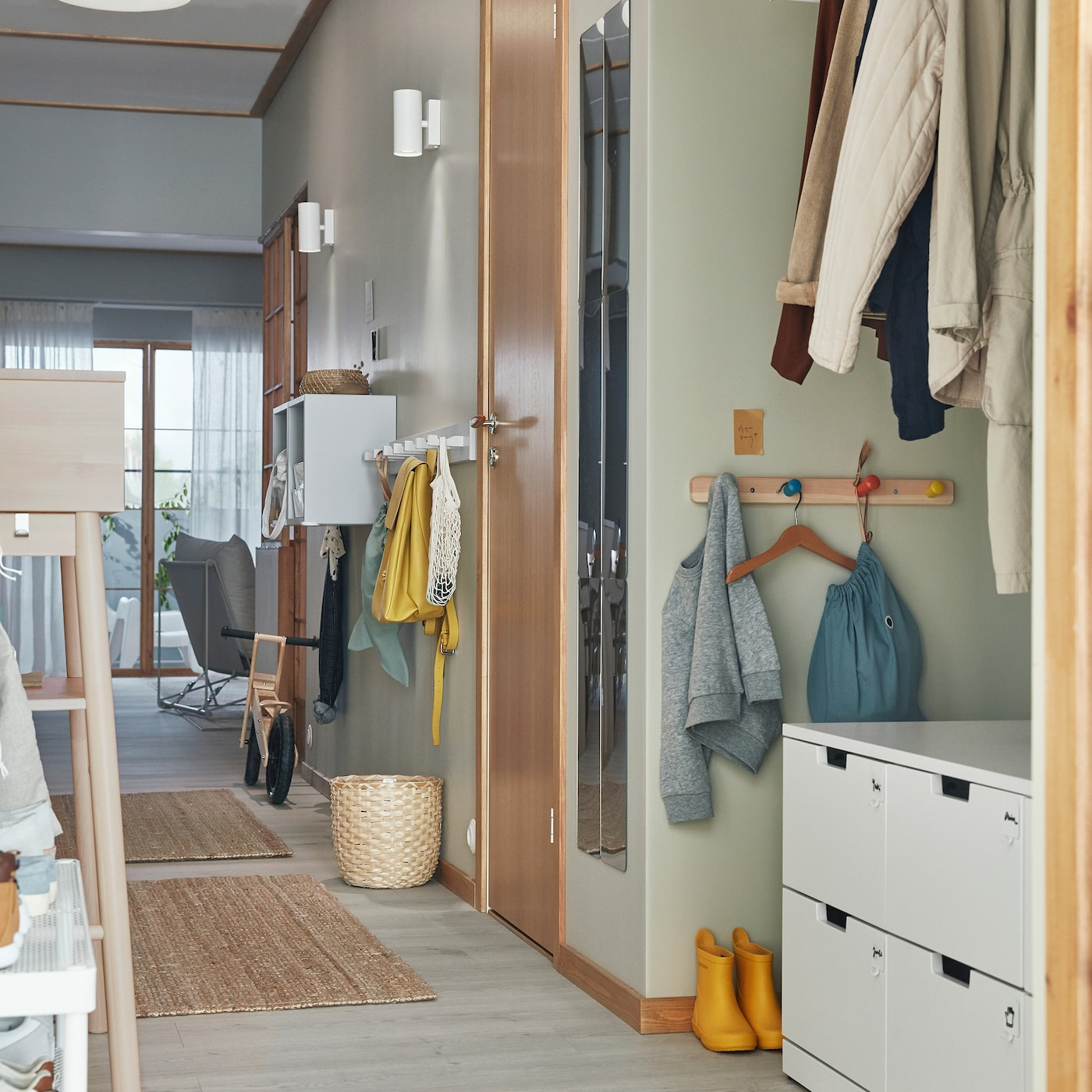 大人も子どもも使えるように、フック付きラックや引き出し付きチェストなどの便利な収納を置いた狭い玄関。