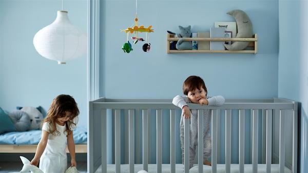 Modrá detská izba, v ktorej je dievčatko a batoľa v postieľke.