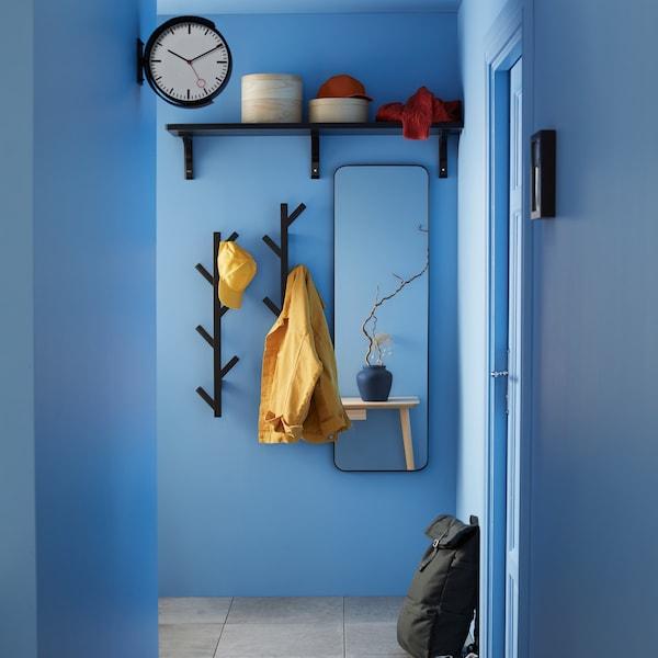 Modrá předsíň se zrcadlem, věšáky a policí.