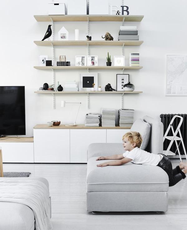 Modulu-sofa batean jolasten dagoen haurra, kolore monokromatikoko konbinazioa duen egongela irekian.