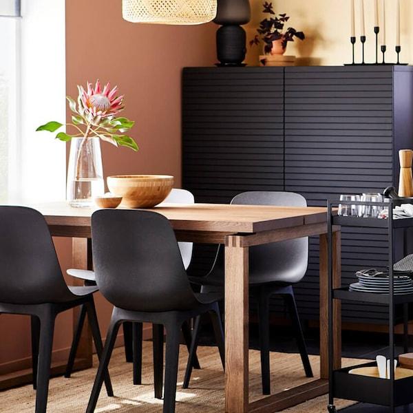 MÖRBYLÅNGA-tammiviilupöytä ja mustat ODGER-tuolit ikkunan vieressä, musta kaappi ja tarjoiluvaunu, jossa on astioita.