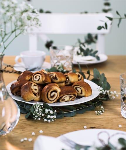 Mohnschnecken auf einem weißen Teller auf einem gedeckten Holztisch