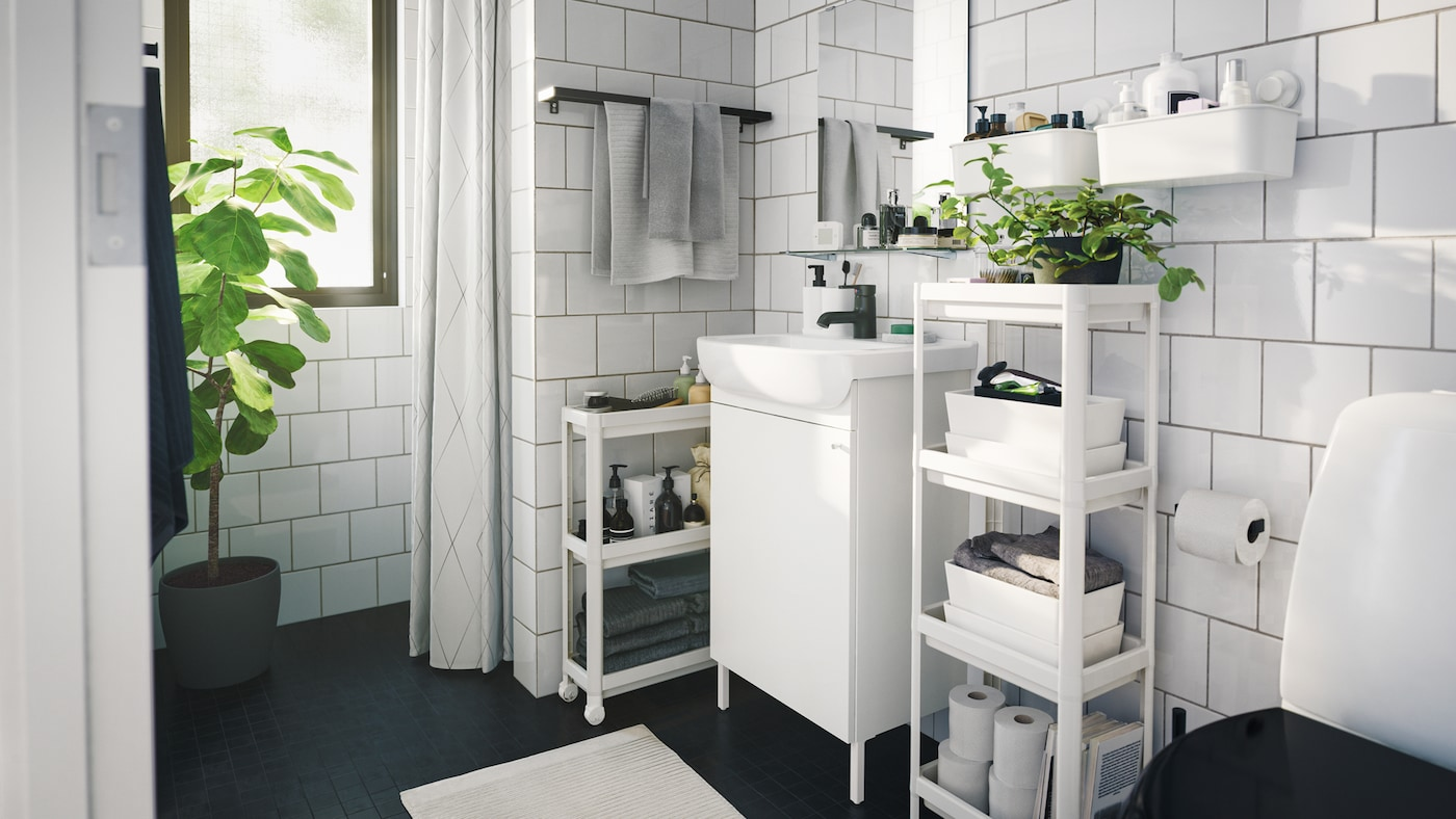 Monochromatic contemporary styled bathroom with several space saving storage units and boxes and indoor green plants.