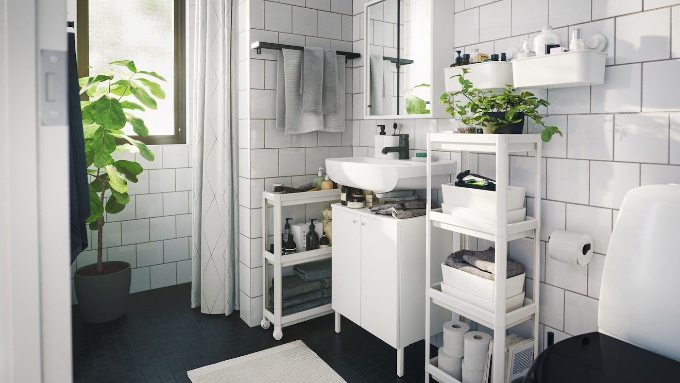 Monochromatic contemporary styled bathroom with several space saving storage units, trolley and indoor green plants.