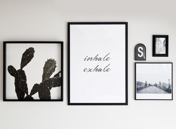 Monochrome prints and quotes in black frames.