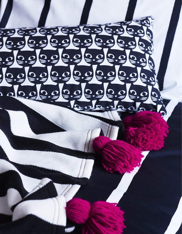 Monochrome textiles with pink tassels.