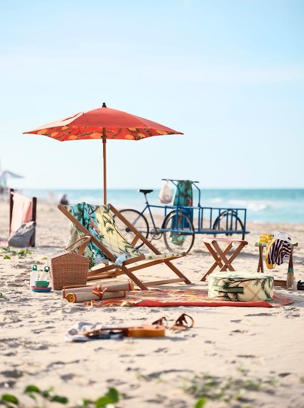 Mønstret strandstol, en parasol og håndklæder på en sandstrand. I baggrunden står en blå cykel.