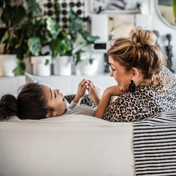 Mor och dotter sitter i en soffa och skrattar och ler.