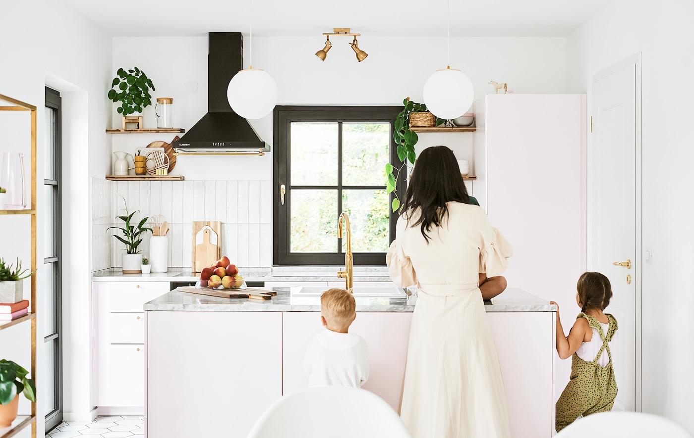 Mor og to børn står ved en køkkenø med lyserøde skabe, bordplader af marmor og messingfarvede armaturer.