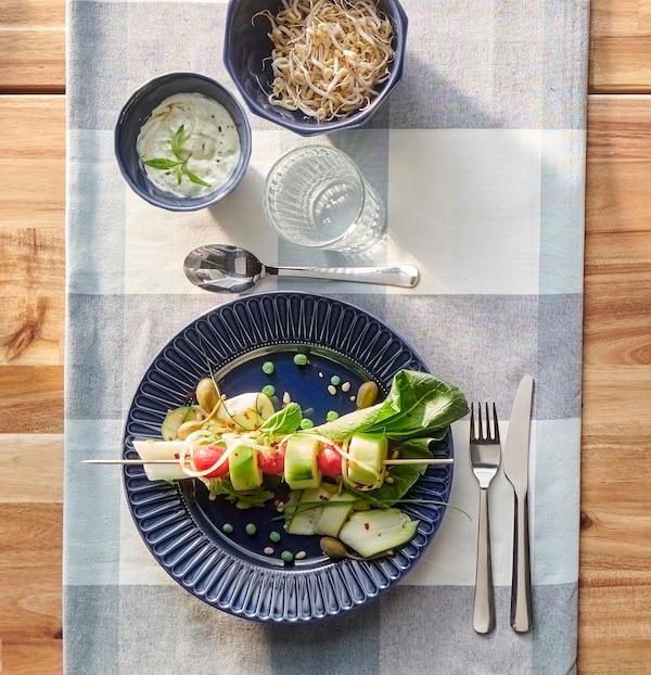 Mørkeblå tallerken med farvestrålende grøntsager på et spyd, MOPSIG bestik og et glas vand på en blåternet dug.