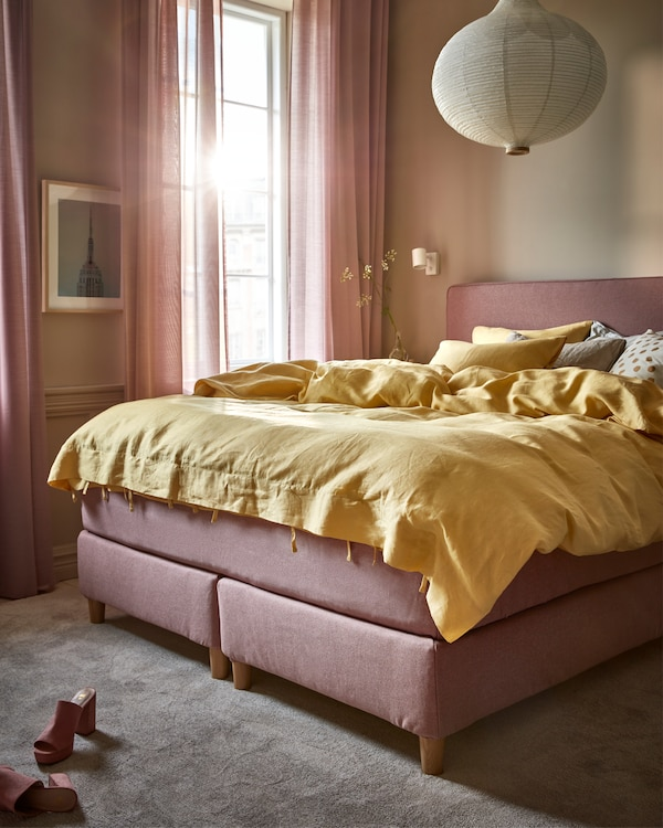 Morning light in a bedroom with a light-brown-pink divan bed, a yellow quilt cover and a white round pendant lamp.