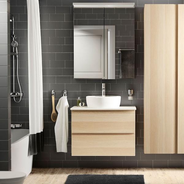 Mosdó és mosdószekrény egy sötét csempéjű fürdőszobában.