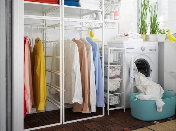 Mosókonyha, JONAXEL fehér polcos elemmel, ruhasínekkel, mosógéppel és szennyeskosárral.