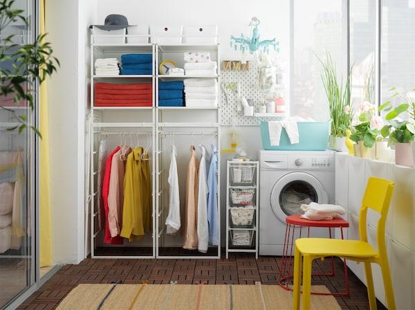 Mosókonyha JONAXEL fehér polcos elemmel, törölközőkkel a polcokon, ruhákkal a síneken és mosógép.
