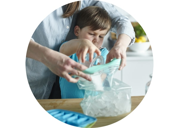 Mother and son are filling an ISTAD plastic bag with ice cubes.