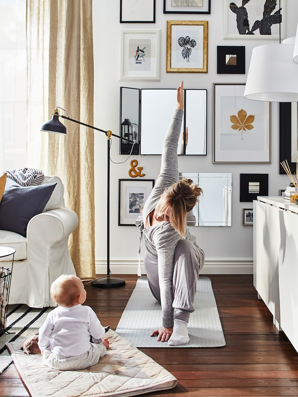 Mother doing yoga on a mat in a living room with a baby sitting on a mat watching her with sofa, sideboard and pictures.