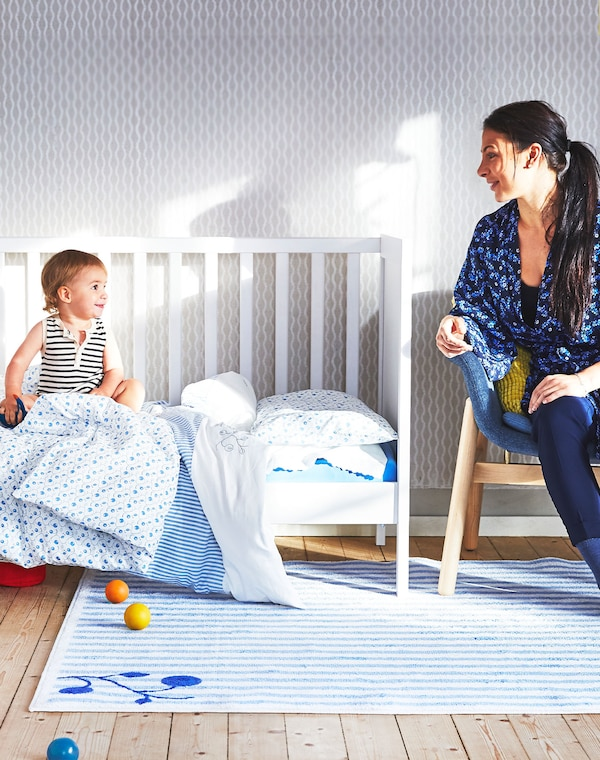 Mother sitting on a wooden chair and baby sitting in white open-sided crib with blue textiles both looking at each other.
