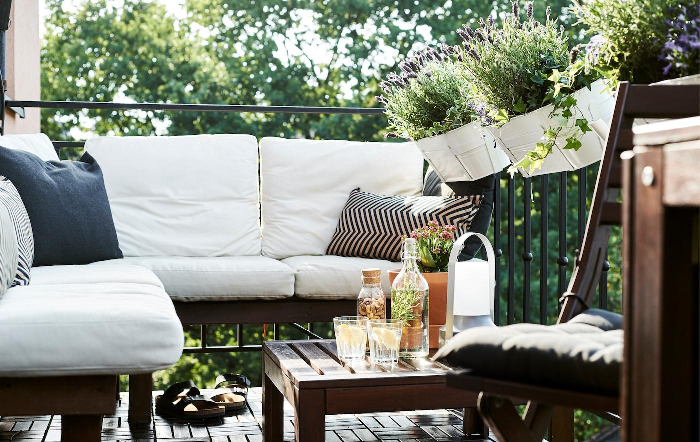 Móveis em madeira escura com almofadas brancas numa varanda com vasos de plantas.