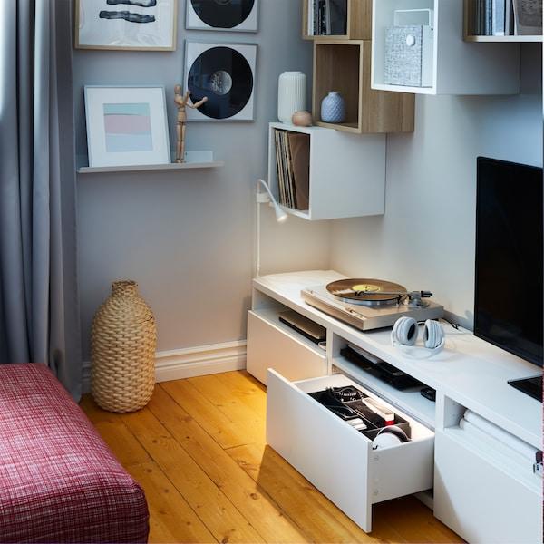 Móvel de TV branco com uma gaveta aberta e iluminada, armários de parede brancos, um pequeno candeeiro de parede e uma jarra decorativa em bambu.