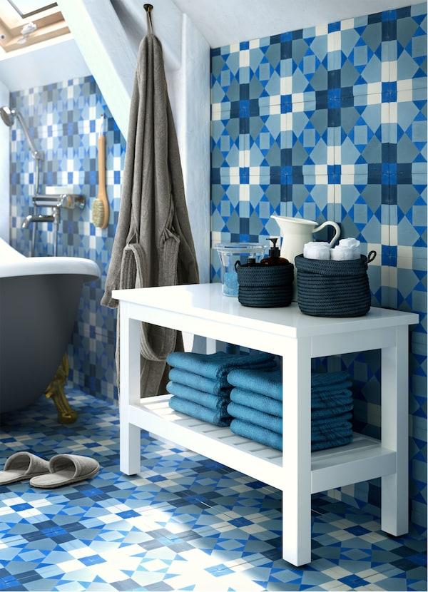 مقعد أبيض HEMNES من ايكيا، عليه سلات زرقاء NORDRANA ومناشف زرقاء في حمام أزرق، ورمادي وأبيض.