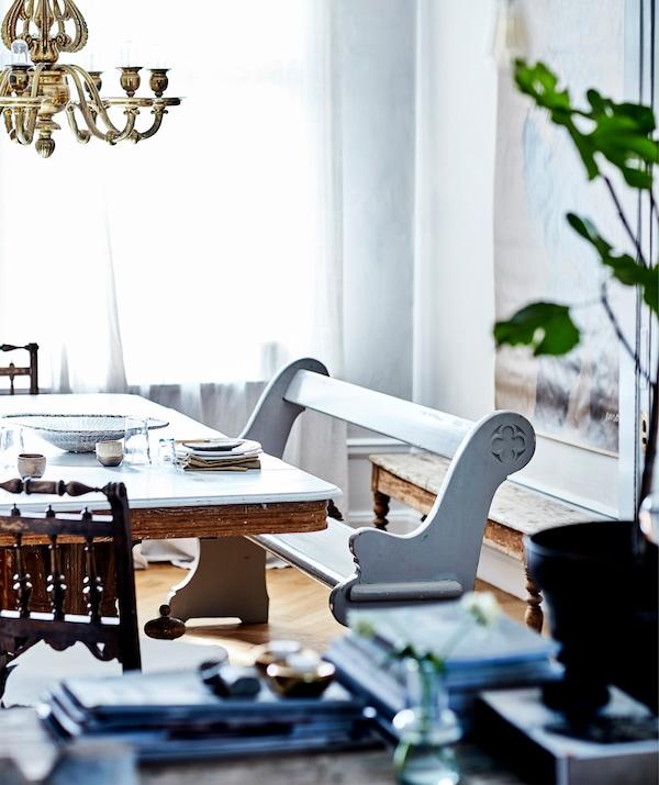 مقعد خشبي أبيض بجانب طاولة مع ثريا ذهبي من أعلى.