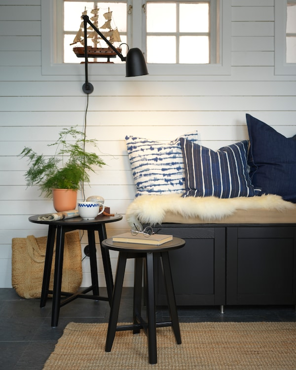 مقعد مطبخ أسود، وسائد زرقاء، وطاولات متداخلة سوداء، ومصباح حائط أسود ونبات أخضر.