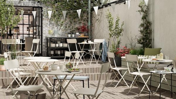 مقهى خارجي يحتوي على طاولات وكراسي من الفولاذ البيج قابلة للطي، ورايات بيضاء، وأرضيات من البلاط ومنصة لتقديم الطعام.