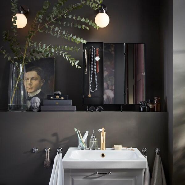 مرآة سوداء، مزهرية مع يوكاليبتوس، مصباحان دائريان مثبتان على الحائط ووحدة حوض غسل بيضاء.