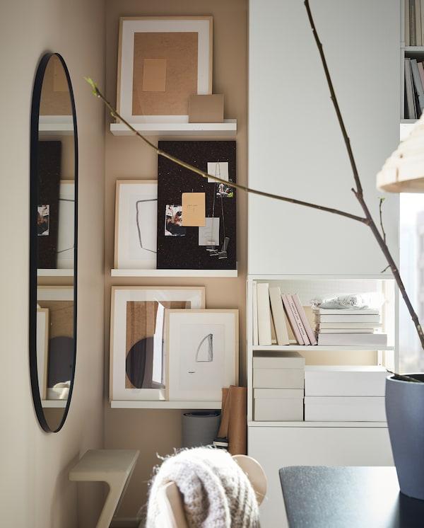 مساحة ضيقة من الحائط تتضمن رفوف صور بيضاء. معروض هنا لوحة ملحوظات SVENSÅS بلون بني داكن وإطارات صور بها أعمال فنية.