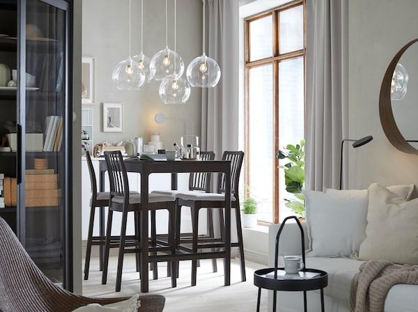 مساحة غرفة طعام بها طاولة مرتفعة بني داكن EKEDALEN تتسع لأربعة أفراد ومقاعد مرتفعة وأغطية مصابيح زجاج شفاف JAKOBSBYN.