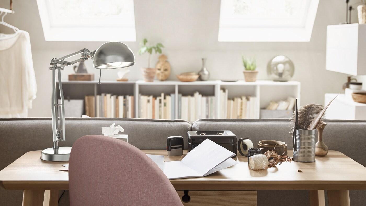 مساحة مكتب منزلي بها مكتبLISABO من قشرة خشب الدردار خلف كنبة، ومصباح عملFORSÅ وكرسي دوارGUNNARED.