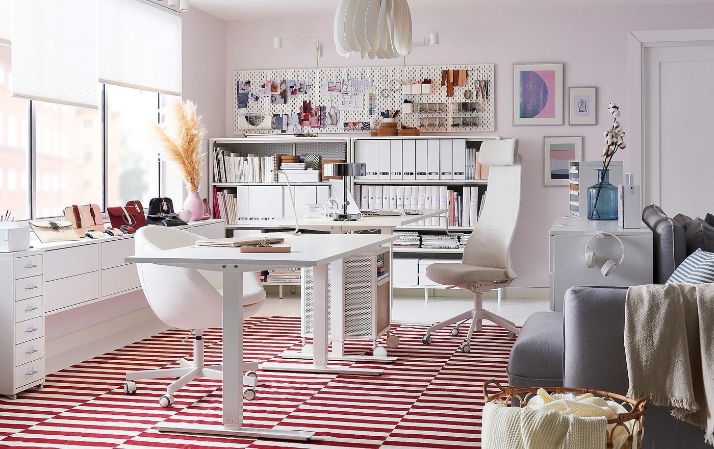 مساحة مكتب منزلي بيضاء مزينة بسجادة حياكة مسطّحة بيضاء وحمراء STOCKHOLM مع وحدة تخزين على عجلات BEKANT بيضاء اللون قابلة للنقل وأدراج مكتب GALANT بيضاء.