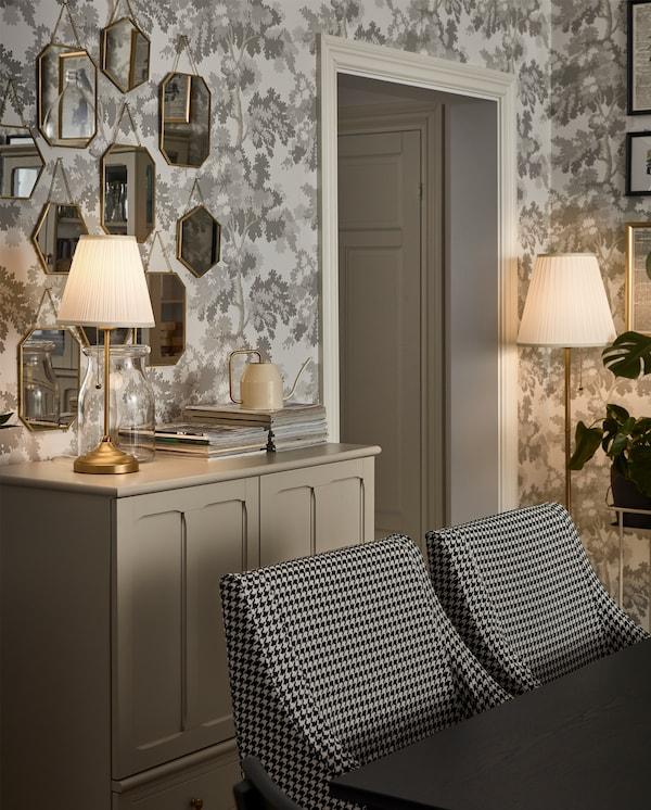 مصباح حائط يصلح لكل الأزمان باللون الأبيض / النحاسي على خزانة باللون البيج الفاتح ويوفر ضوءًا ناعمًا وزخرفيًا بجانب طاولة طعام.