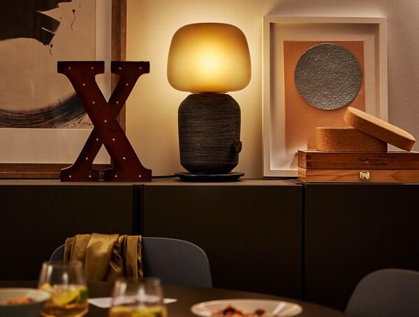 مصباح مع مكبرات صوت واي فاي SYMFONISK إلى جانب إكسسوارات زينة على خزانة غرفة طعام.