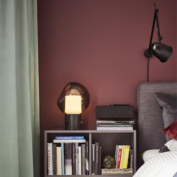 مصباح طاولة رمادي من الزجاج والنحاس، وسرير طويل رمادي، ومصباح حائط أسود وخزانة رمادية داكنة.